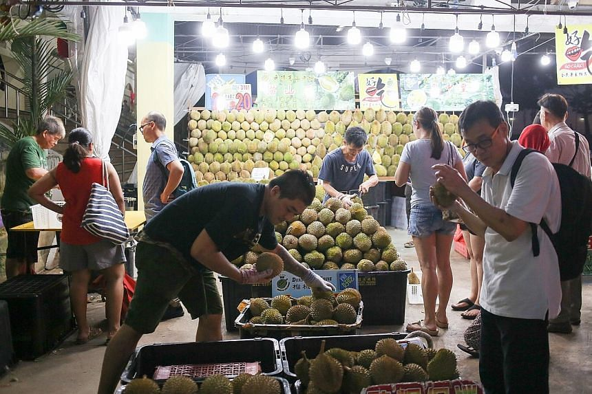 Mr Sky Teo (foreground, left), stall manager of Durian Fullhouse near Kovan market and food centre, said sales may not increase even though he is bringing in 30 55kg cartons of durians a day.