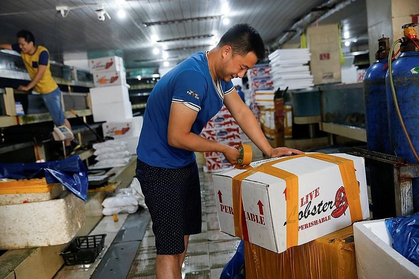 A customer seals a box of US lobsters at a fish market in Beijing. China has said it will impose tariffs on US goods including pork, seafood, cotton and soya beans.