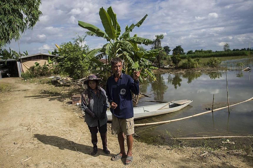 Mr Lek Lapdaungpoin and his wife Koung at their farm flooded by water pumped from Tham Luang cave.