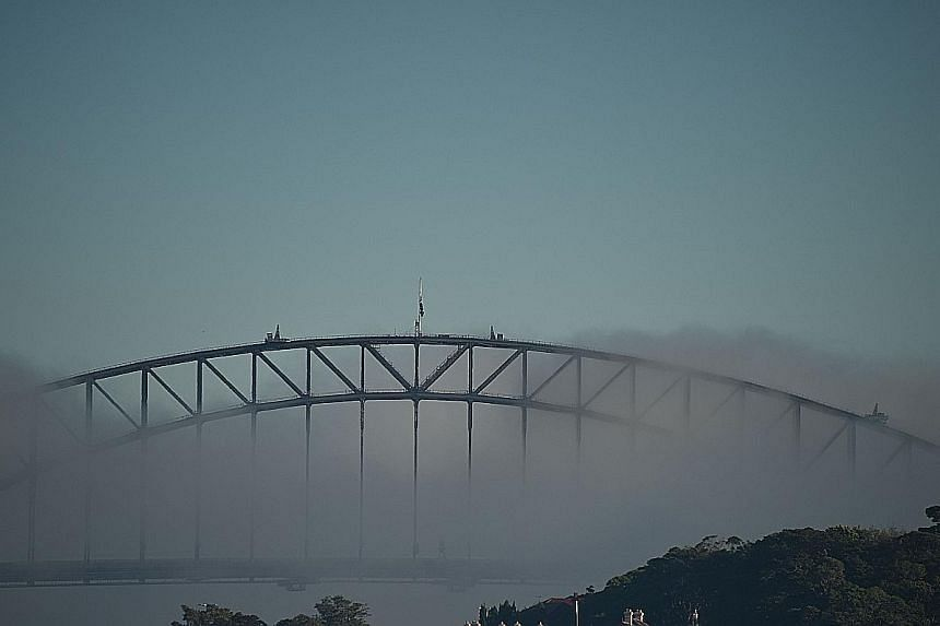 The Harbour Bridge nearly disappearing from sight as Sydney was shrouded in fog yesterday. Some flights were delayed or diverted, while ferry services were cancelled.