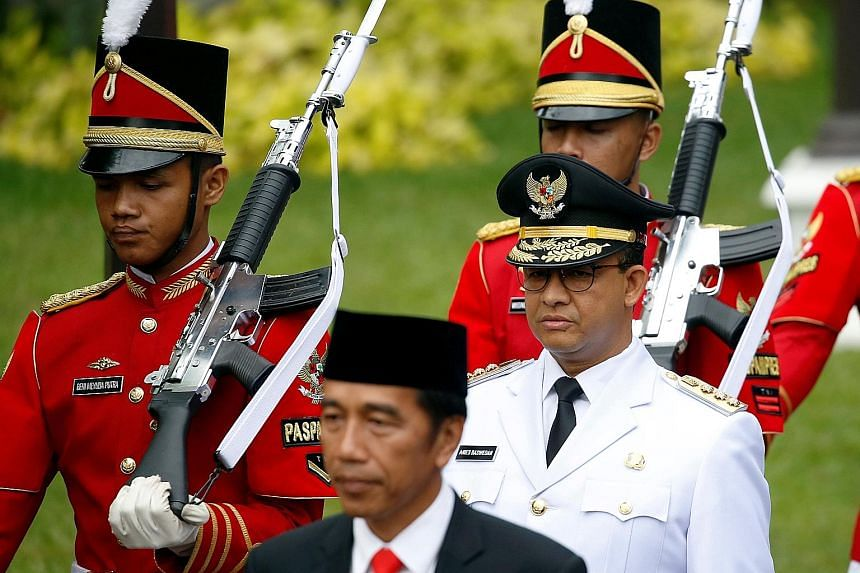 Indonesian President Joko Widodo with Jakarta Governor Anies Baswedan (in white) at Mr Anies' swearing-in ceremony in Jakarta last October. Voting for Indonesia's next president will take place on April 17 next year.