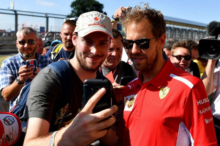 Vettel (right) poses for a photograph with a fan at Silverstone motor racing circuit.