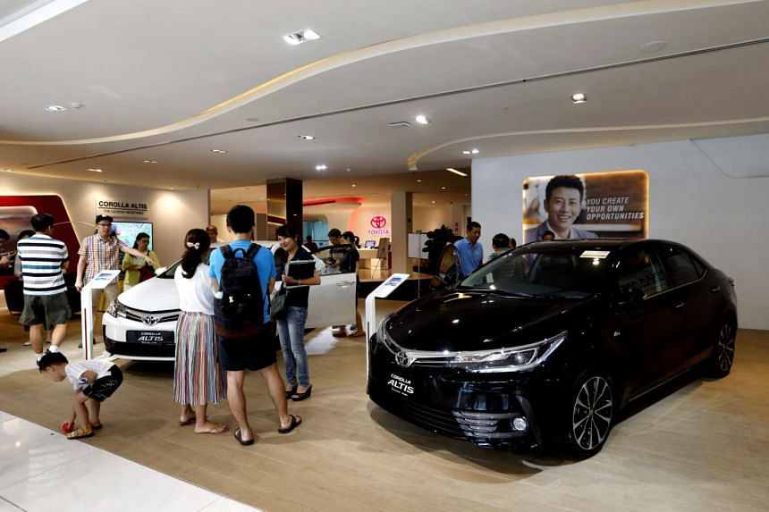 File photo showing customers at Borneo Motors' Toyota showroom. The COE price for cars above 1,600cc or 130bhp has dropped by 8.6 per cent to $31,000.