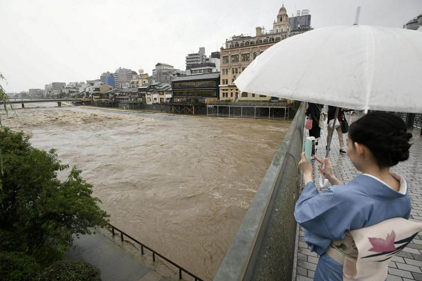 A kimono-clad woman taking photos of swollen Kamo River, caused by a heavy rain, from Shijo Bridge in Kyoto, western Japan, on July 5, 2018.