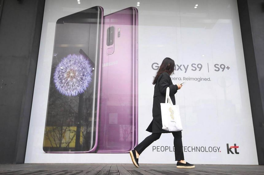 A woman walks past an advertisement for the Samsung Galaxy S9 at a mobile phone shop in Seoul, South Korea.