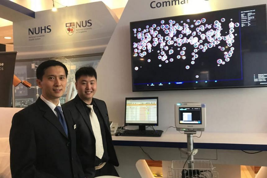 Dr Ngiam Kee Yuan, NUHS's group chief technology officer (left), and Dr Feng Mengling, assistant professor from the NUS Saw Swee Hock School of Public Health, presenting the Command Centre, part of NUHS' new artificial intelligence system, Discovery