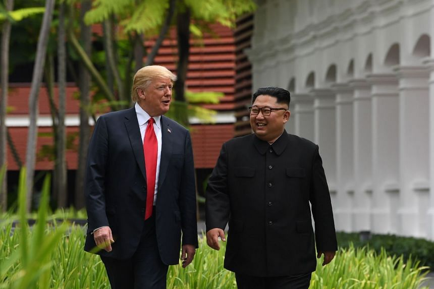 Trump (left) walking with Kim during a break in talks at their historic US-North Korea summit in Singapore.