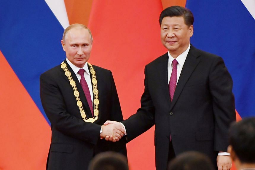 Chinese President Xi Jinping (left picture, at right) congratulates Russian President Vladimir Putin after presenting him with the Friendship Medal in Beijing last month. The writer says that their shared strategic goal has long been to put an end to