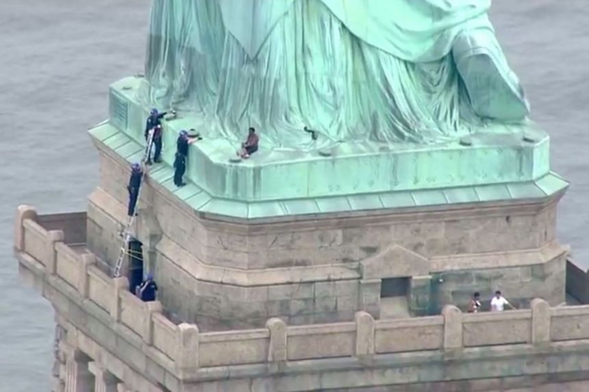 Police talking to a woman who climbed to the base of the Statue of Liberty in New York on July 4, 2018.