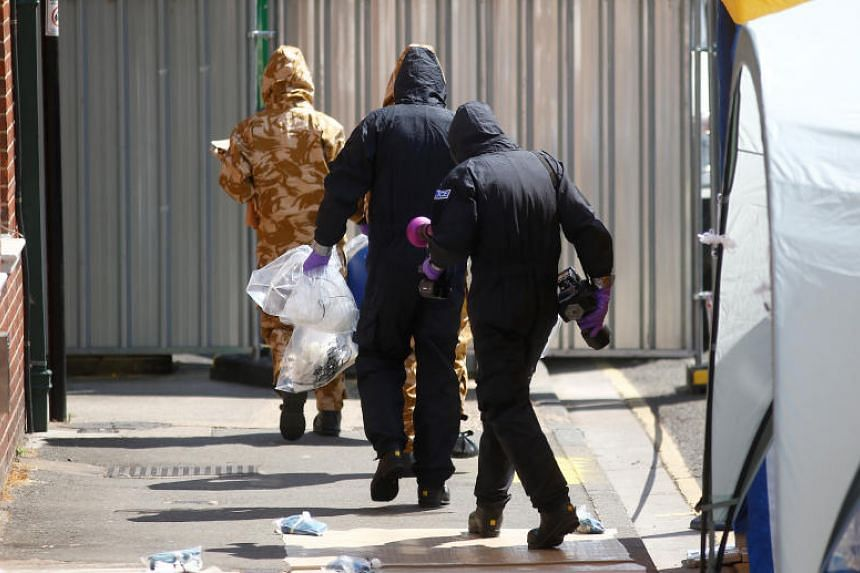 Forensic investigators wearing protective suits enter the rear of John Baker House, after it was confirmed that two people had been poisoned with the nerve-agent Novichok, in Amesbury, Britain, on July 6, 2018.