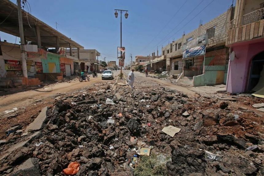 A Syrian civilian walks past a shell hole after Syrian government forces recently recaptured the village of Ghariyah ash Sharqiyah from the rebels, in the province of Deraa, on July 4, 2018.