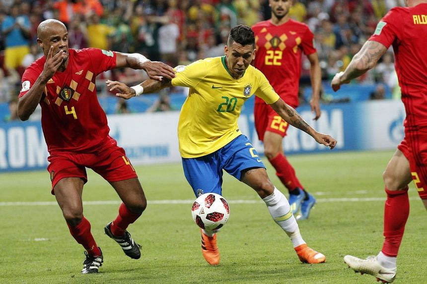 Roberto Firmino of Brazil (centre) and Vincent Kompany of Belgium (left) in action.