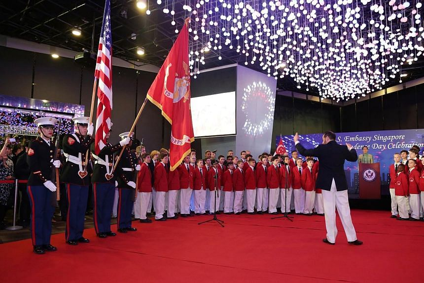 United States Marines yesterday during the Presenting Of The Colours ceremony as the world-renowned Philadelphia Boys Choir sang the US and Singapore national anthems at the celebration of the 242nd anniversary of the United States' independence, whi