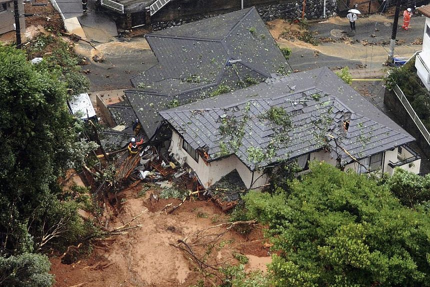 Above: The Togetsu bridge on the Katsura River in Kyoto yesterday. Right: Rescue workers at houses damaged by a landslide in Kitakyushu, southwestern Japan.