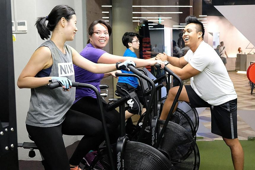 Trainer Fazrul Rozali with some users of the Assault Air Bikes, which are part of a specially devised three-way cardio programme at TripleFit. ST Run participants will get to try out the bikes and the other two components, Ergo Rower and SkiErg.