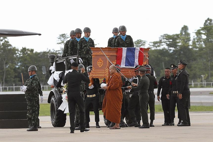 Left: A Thai Buddhist monk leading a military honour guard carrying the coffin of former Thai navy Seal diver Saman Kunan (above) at Mae Fah Luang international airport in Chiang Rai yesterday.