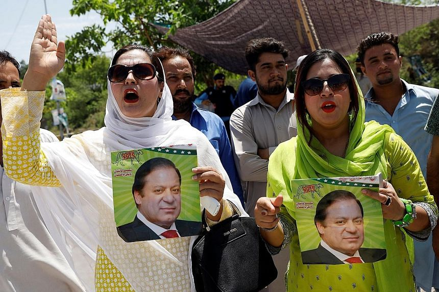Supporters of the PML-N party, with pictures of former prime minister Nawaz Sharif, rallying against the verdict against him in Islamabad yesterday. His daughter and her husband were also given jail sentences.