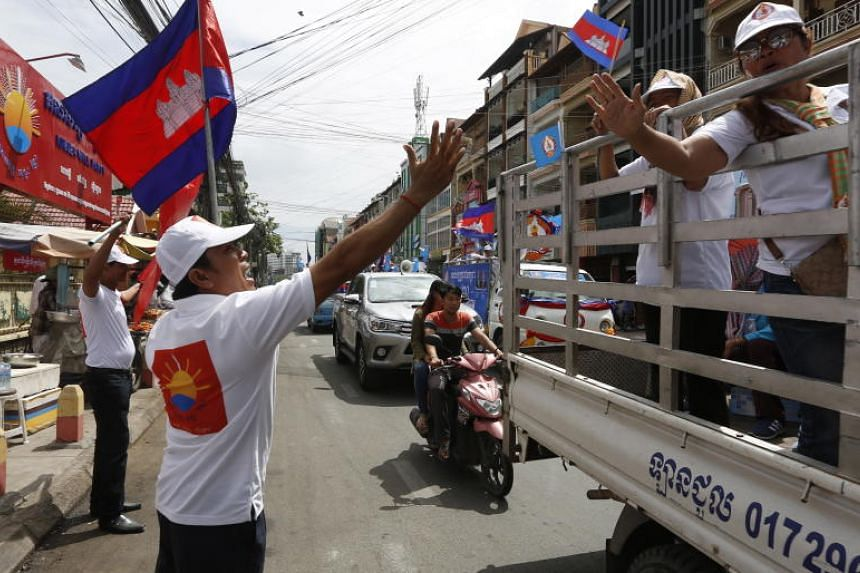 A supporter of the Khmer Will Party (left) greets supporters of the Cambodian People's Party during political campaigning in Phnom Penh, Cambodia, on July 7, 2018.