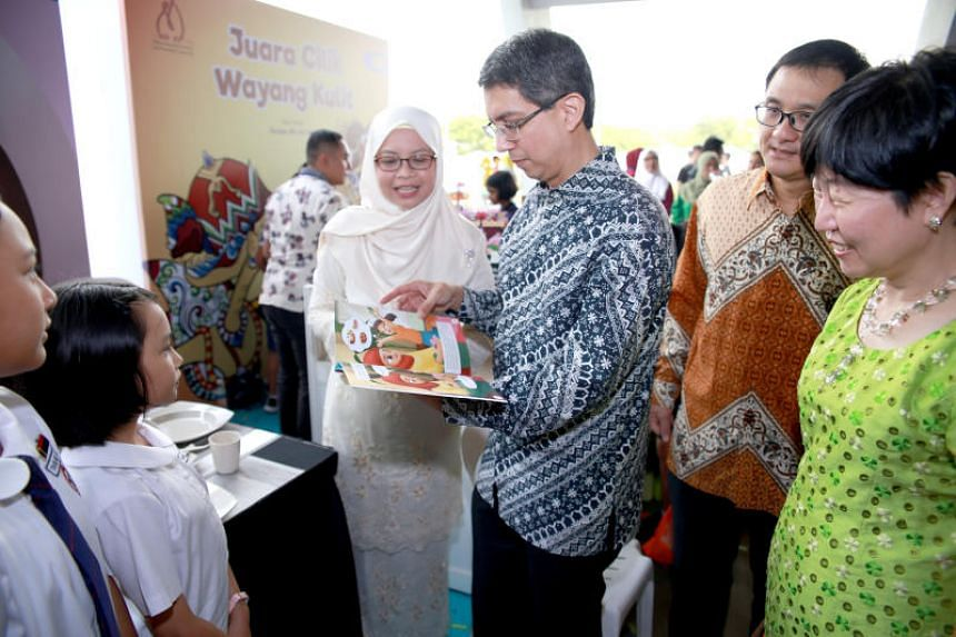 Senior Parliamentary Secretary for Education, Associate Professor Muhammad Faishal Ibrahim, looks at one of the 20 new Nabil Nabilah Reader Series titles that have been launched for Primary 3 and Primary 4 pupils.