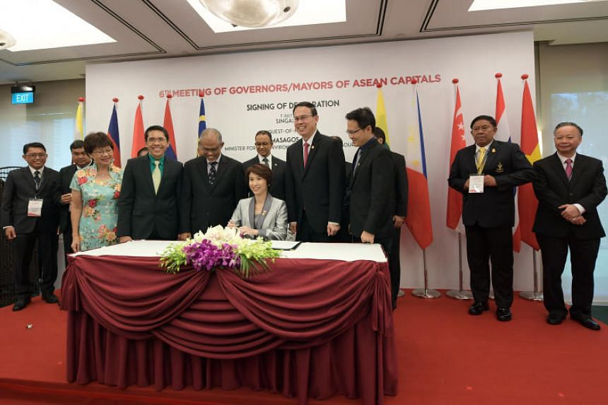 Singapore's Chairman of Mayors' Committee and Mayor of South West District Ms Low Yen Ling (seated), signing the Singapore Declaration as other officials and delegates look on.