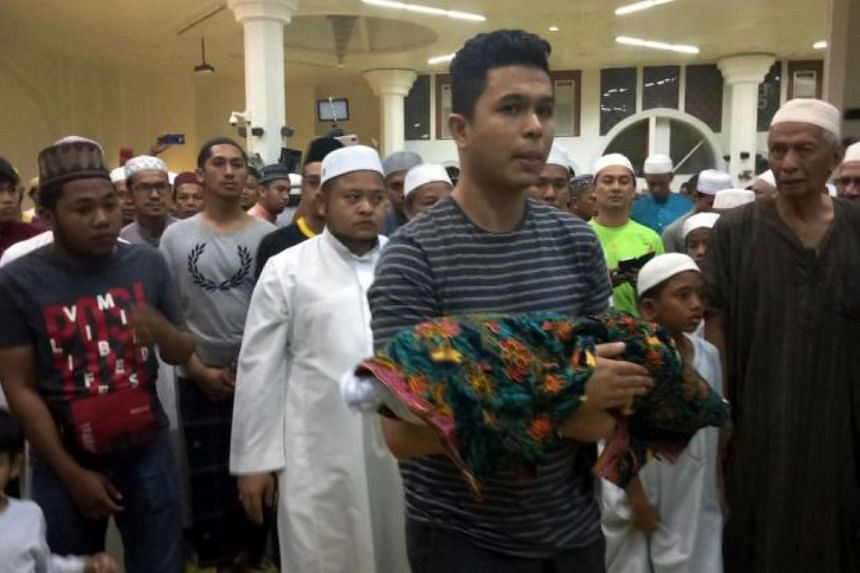 Adam Rayqal's father, Mr Mohd Sufi Naeif, taking his son's body, for funeral prayers at Al-Muktafi Billah Shah Mosque in Kuala Terengganu on July 4.