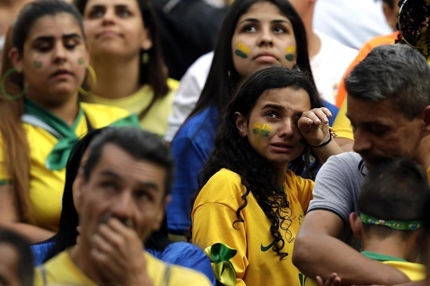 Brazilian fans looking dejected after their team's defeat during the World Cup match against Belgium, at a public screening event in Rio de Janeiro, Brazil, on July 7, 2018.