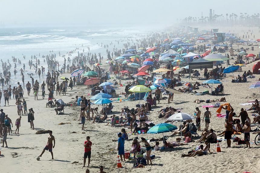Thousands of beachgoers cooling off as all-time record breaking heat envelopes Southern California, in Huntington Beach, California, on July 6, 2018.