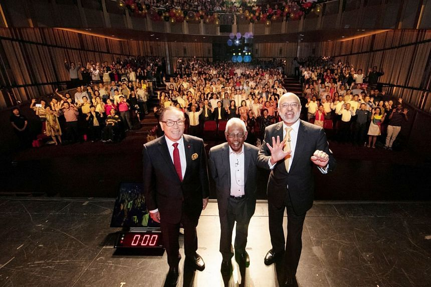 Above: (From left) DBS chairman Peter Seah, former chairman S. Dhanabalan and chief executive Piyush Gupta at a special Golden Jubilee employee townhall held at Victoria Theatre yesterday. Left: Bank employees celebrating at Victoria Theatre. The gro