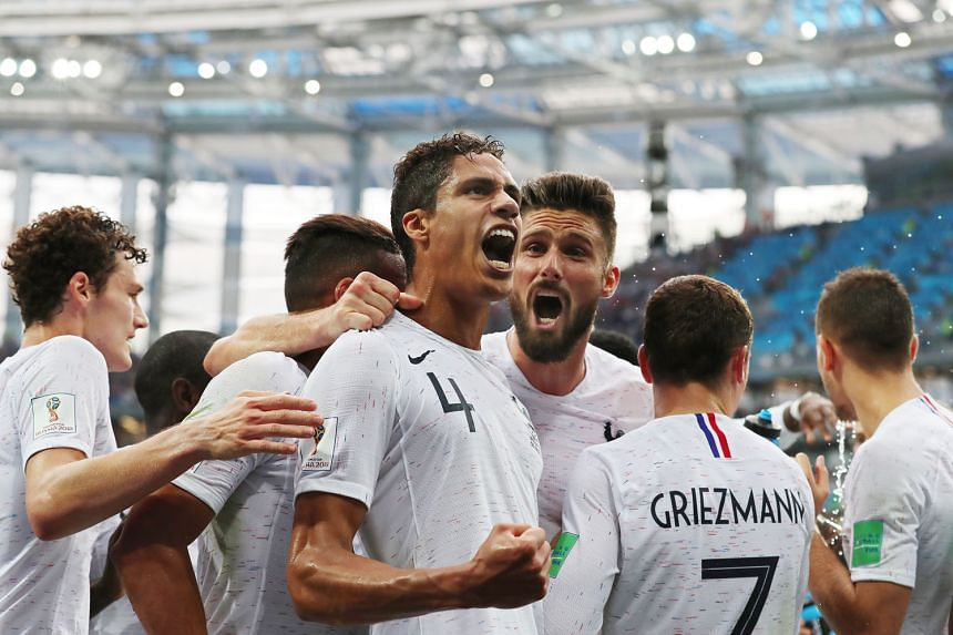 A delighted Raphael Varane celebrates with his team-mates after putting France ahead against Uruguay, who lacked bite with their striker Edinson Cavani left out after failing to recover from a calf injury.