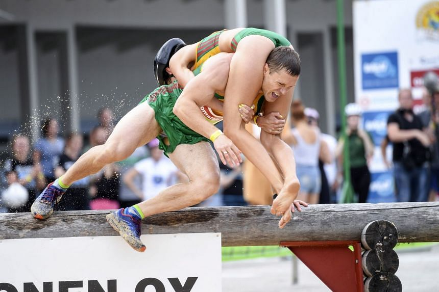 Vytautas Kirkliauskas and Neringa Kirkliauskas of Lithuania take part in the annual Wife Carrying World Championships.