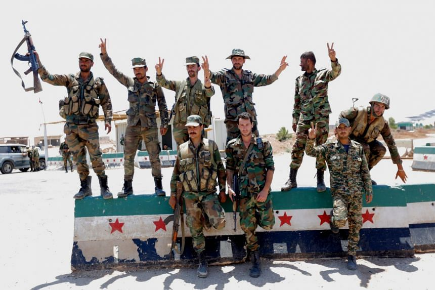 Syrian soldiers flash the victory sign at Nassib border crossing in the southeastern countryside of Daraa city.