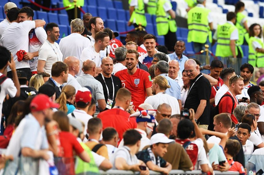 Harry Kane (centre) celebrates with fans after the match.