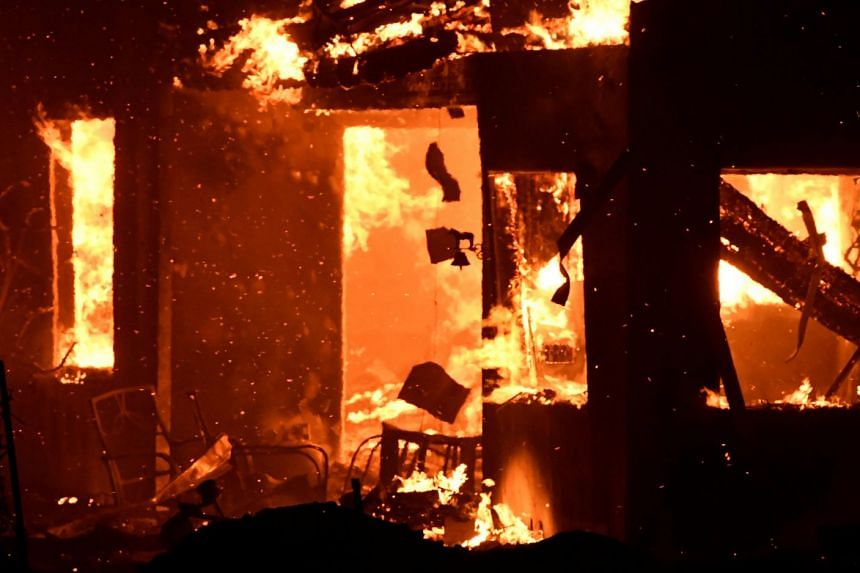 A house burns as firefighters battle a fast-moving wildfire that destroyed homes in Goleta, California.