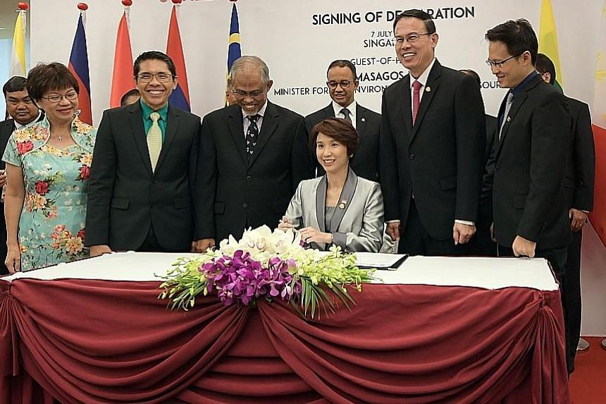 (Front row from left) Mayor Denise Phua, Mayor Maliki Osman, Environment and Water Resources Minister Masagos Zulkifli, Mayor Teo Ho Pin and Mayor Desmond Choo gathering around Ms Low Yen Ling, chairman of the Mayors' Committee, as she signs the Sing