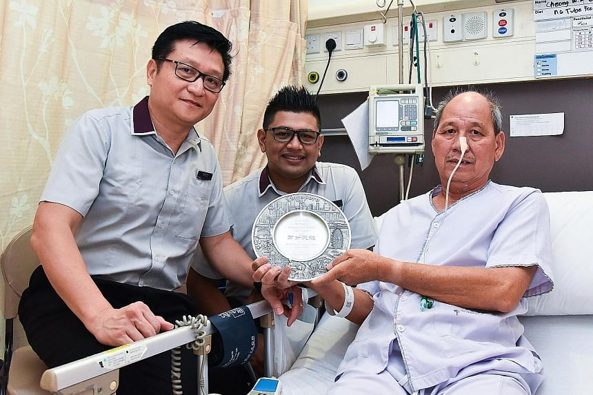 Station manager Fong Sai Weng and assistant station manager Abdul Azim Abdul Azizam visiting Mr Cheong Weng Kuen in hospital on Friday. Mr Cheong made a plaque and presented it to the SBS Transit duo to thank them.