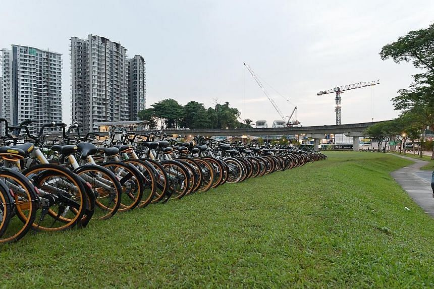 Rows of oBikes spotted at a field in Seng Kang early on Wednesday last week. Observers say the current dockless bike-share system - in which companies flood the market with two-wheelers and charge below-cost rates - is unsustainable.