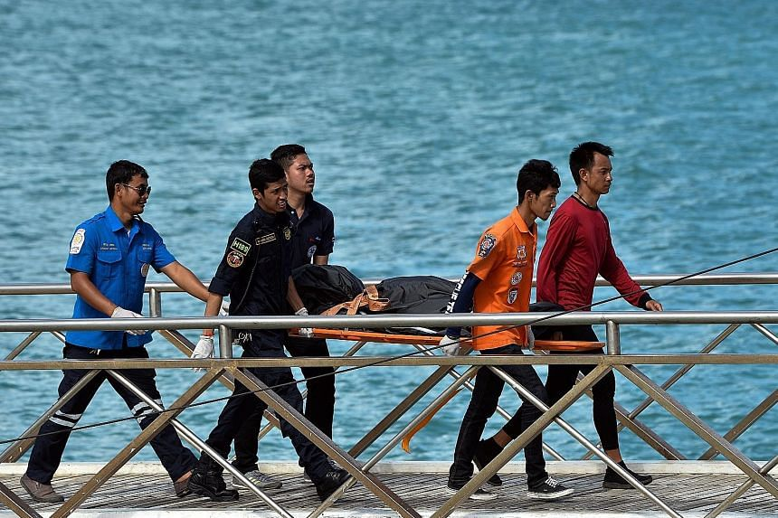 Thai rescue workers carrying the body of a victim on Friday. The Chinese government has pressed for a speedy investigation into the cause of Thursday's disaster, while Thai Deputy Prime Minister Prawit Wongsuwan has ordered a probe into why the boat'