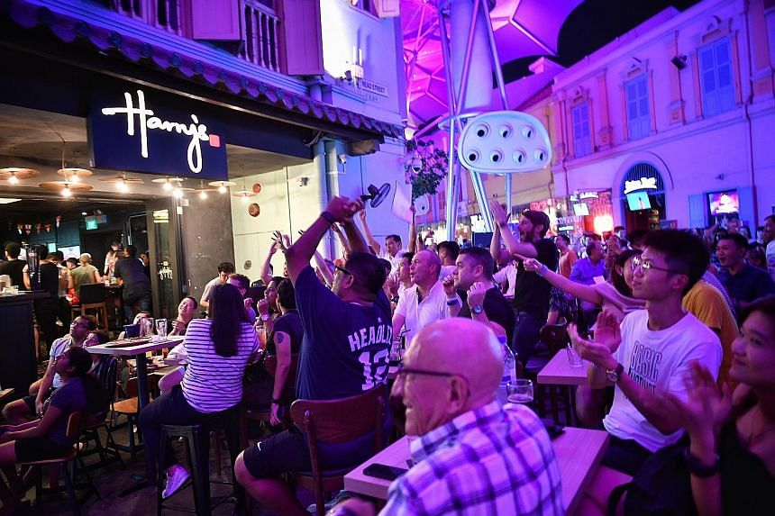The crowd cheering at Harry's Bar in Clarke Quay during the World Cup quarter-final between Sweden and England yesterday. Fans watching the live screening of the match in comfort at the Resorts World Sentosa's Football Fever event.