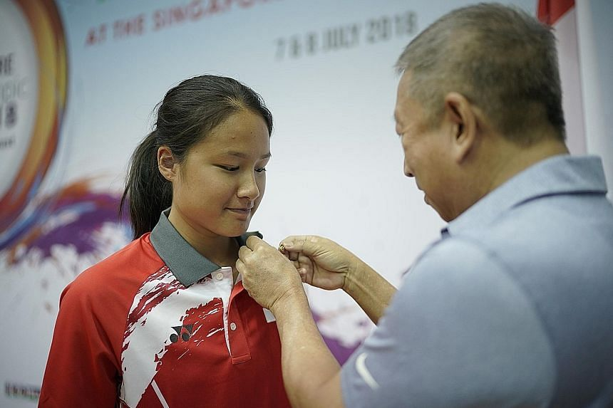 Short track speed skater Cheyenne Goh receiving the Olympic Participation Lapel Pin from Singapore Olympic Foundation chairman Ng Ser Miang at the opening ceremony of the 7th Singapore Youth Olympic Festival (SYOF) at the Toa Payoh Sports Hall yester