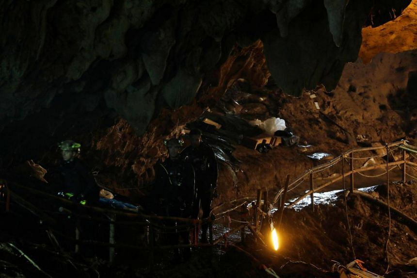 Divers walk inside Tham Luang cave complex, where 12 schoolboys and their soccer coach are trapped inside a flooded cave, on July 7, 2018.