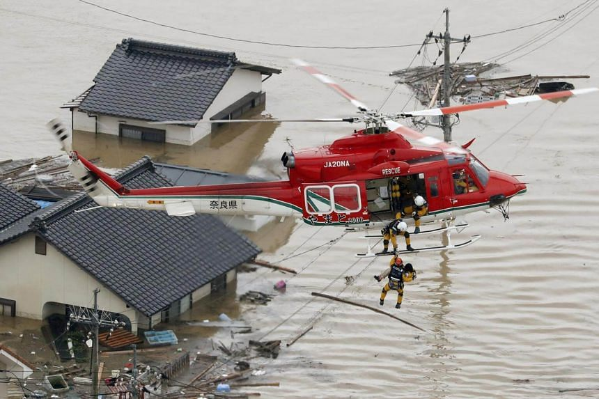 A local resident being rescued from a submerged house by rescue workers using helicopter at a flooded area in Kurashiki, southern Japan, on July 7, 2018.