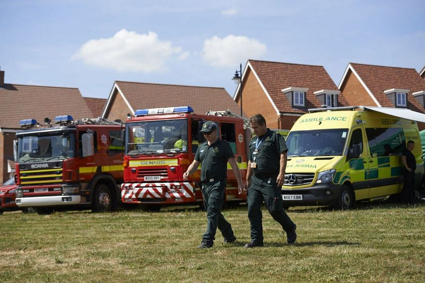 Fire trucks and emergency response vehicles are parked outside a residential house in Amesbury, southern England.