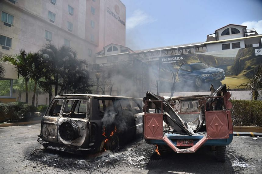 Cars burn in a hotel parking lot in Port-au-Prince after protesters set them on fire on July 7, 2018.