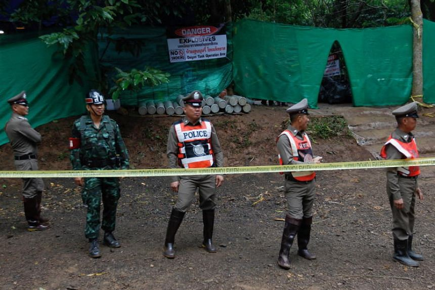 Thai police officers and military personnel stand guard near Tham Luang cave in Chiang Rai province on July 8, 2018, during the ongoing rescue operation for 12 boys and their football coach trapped inside.