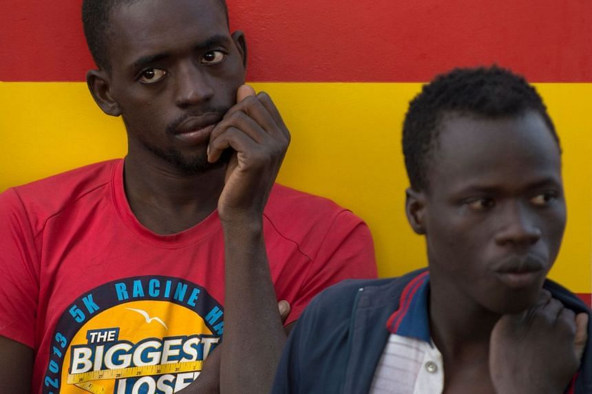 Migrants wait on a Spanish coast guard boat upon their arrival at Malaga's harbour on July 7, 2018, after an inflatable boat carrying 56 migrants was rescued by the Spanish coast guard off the Spanish coast.