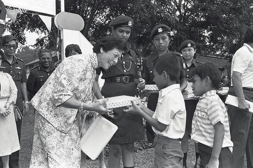Mrs Wee presenting gifts to children during a police fun fair and carnival in 1985 at the then Police Academy in Thomson Road.