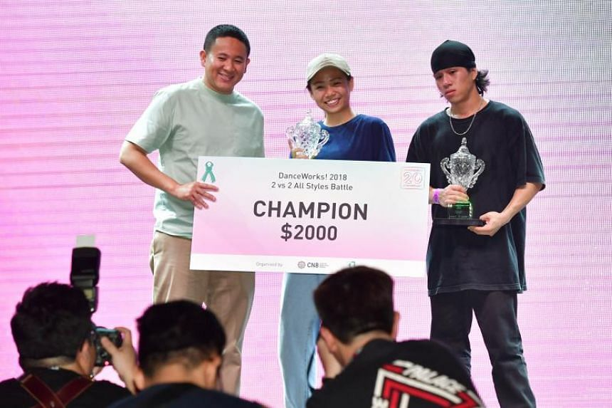 DanceWorks! winners Joey Tan and Gerald Chan receiving the cash prize and trophy from Senior Parliamentary Secretary for Home Affairs and Health Amrin Amin on July 8, 2018.