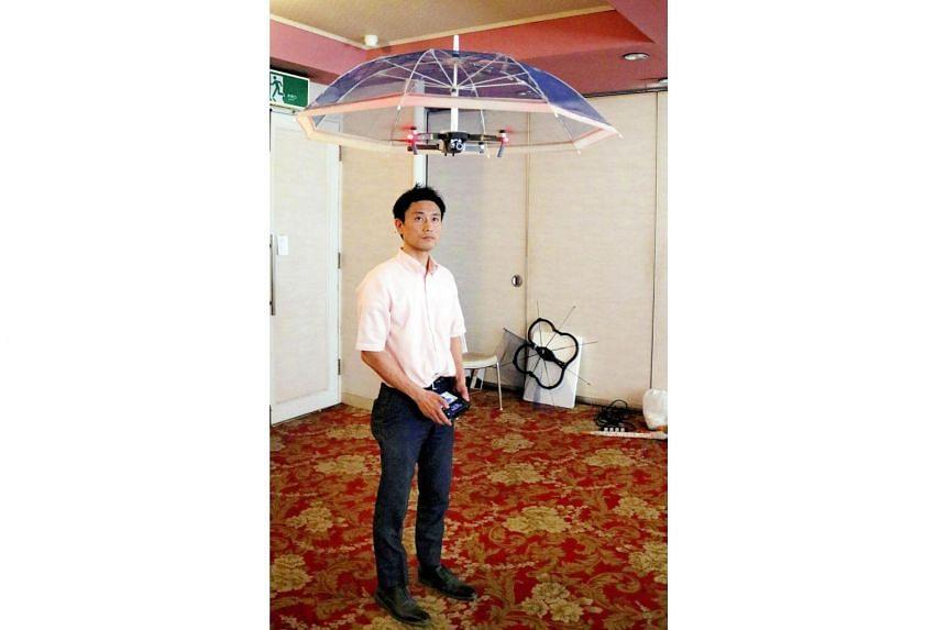 Asahi Power Service president Kenji Suzuki flying a prototype of the drone umbrella, in Oyama, Tochigi Prefecture.