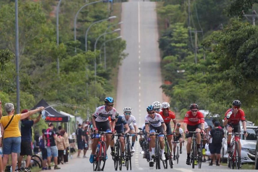 Participants of the OCBC Cycle National Road Championship cycling on a road in Batam on July 8, 2018.