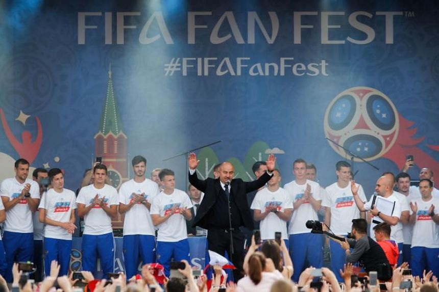 Russia's national football team coach Stanislav Cherchesov and players are greeted by fans during a visit to the Moscow's fan zone on July 8, 2018.